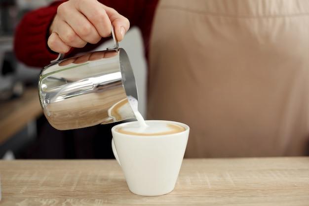 Barista gießt milch vom metalltopf zur weißen glasschale auf holztisch. prepait latte