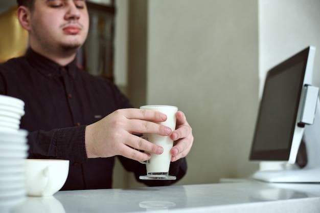 Barista hält eine tasse latte hinter die bar