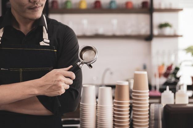 Barista hält einen siebträger für einen kaffee im café. pappbecher hintergrund.