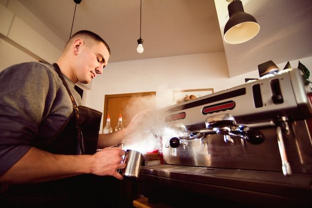 Barista-hände, die kaffeetasse mit kaffeemaschine in der kaffeestube machen