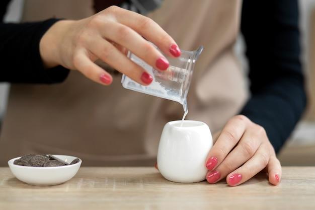 Barista in einer schürze gießt milch in eine tasse. barista arbeitet in einem café