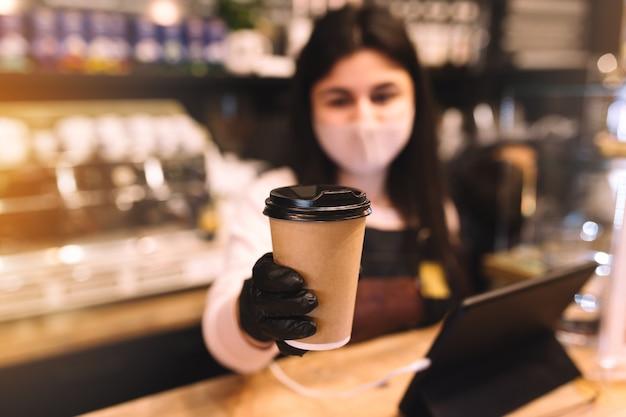 Barista in schützender gesichtsmaske und schwarzen handschuhen gibt im café eine tasse kaffee.
