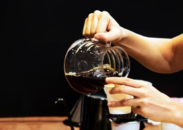 Barista kocht kaffee, barista gießt filterkaffee in glas