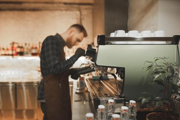 Barista kocht kaffee in einem gemütlichen café.