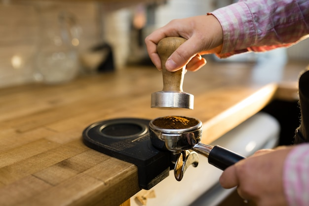 Barista kocht kaffee in einer kaffeemaschine. kaffeehaus