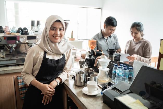 Barista lächelt, wenn er einen kaffee für einen kunden macht