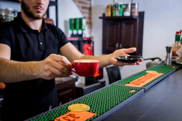 Barista macht cappuccino-kaffee und gießt milch ein.