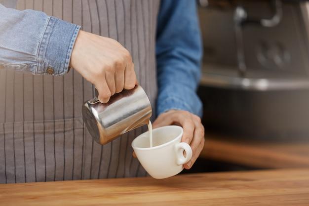 Barista macht eine tasse latte und gießt milch in die tasse.