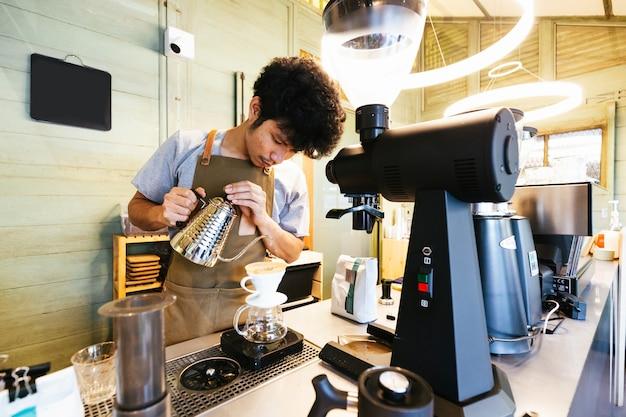 Barista macht kaffee mit der alternativen methode dripping.