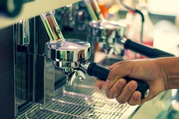 Barista mahlt frisch gerösteten kaffeespezialitäten von hand in eine professionelle maschine.