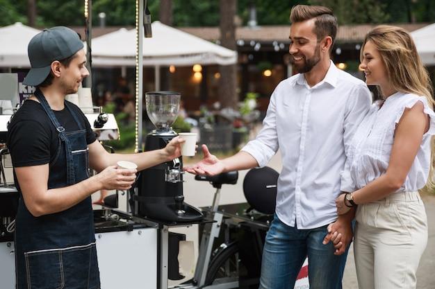 Barista mann, der kaffee an junges paar im beweglichen café auf der straße verkauft