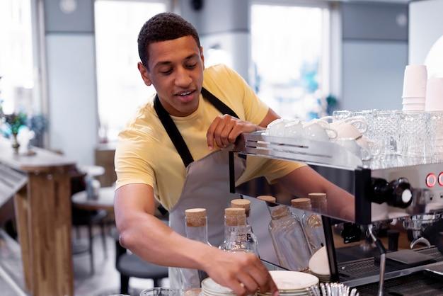 Barista mit mittlerem schuss, der kaffee zubereitet