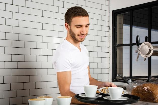 Barista mit tassen kaffee und keksen auf dem tablett
