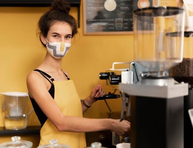 Barista trägt eine gesichtsmaske beim kaffeekochen