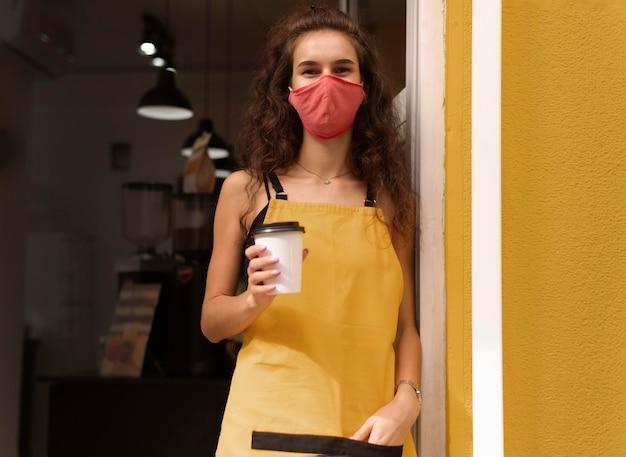 Barista trägt eine gesichtsmaske, während er eine tasse kaffee hält