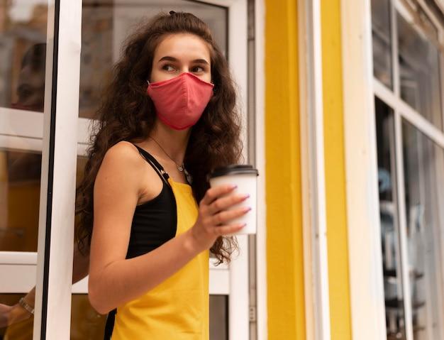 Barista trägt eine gesichtsmaske, während er eine tasse kaffee im freien hält
