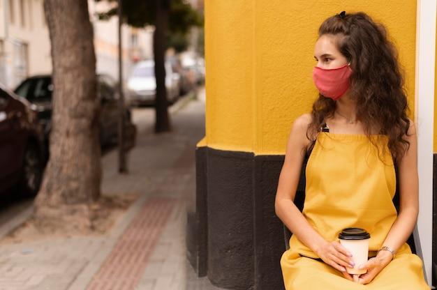 Barista trägt eine gesichtsmaske, während er eine tasse kaffee mit kopierraum hält