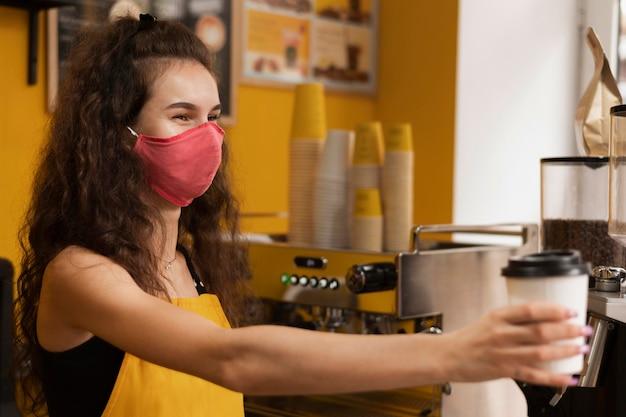 Barista trägt eine medizinische maske, während er eine kaffeetasse gibt