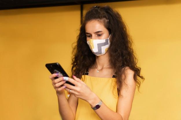 Barista trägt eine medizinische maske, während sie ihr telefon überprüft