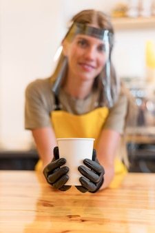 Barista trägt gesichtsschutz beim servieren von kaffee