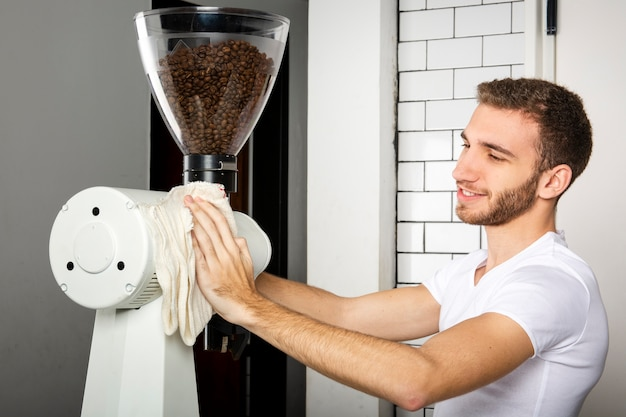 Barista wischt die kaffeemaschine mit einem tuch ab