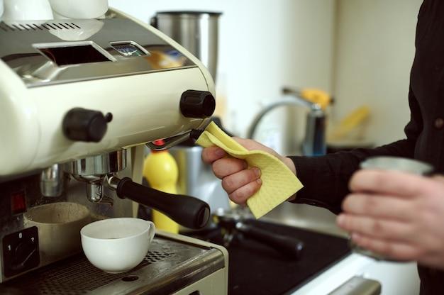 Barista wischt übrig gebliebene milchtropfen auf der kaffeemaschine ab