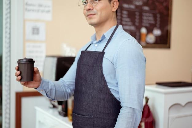 Baristas geben eine tasse heißen kaffee und eine bäckerei, um den kunden im café anzubieten?