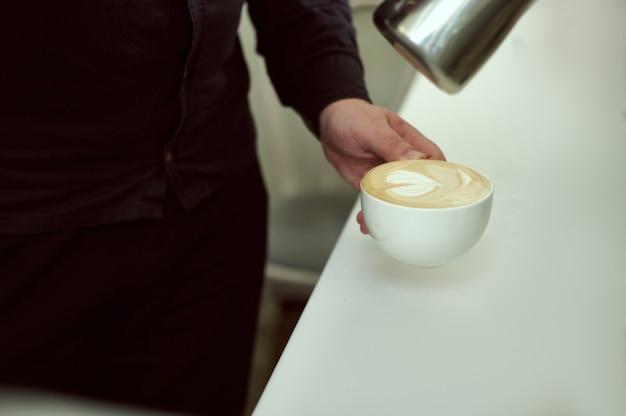 Baristas hand hält eine tasse cappuccino. latte kunst.