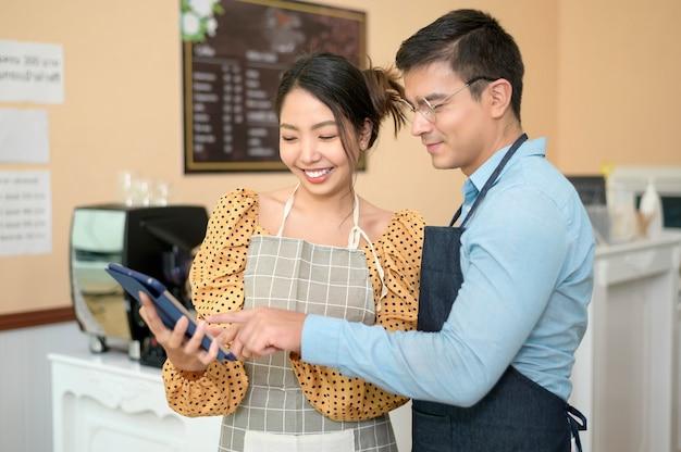 Baristas mit tablet-überprüfung des geschäftseinkommens, erfolgreiches geschäftsmarketing im café