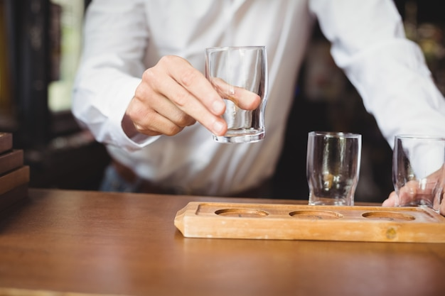 Barkeeper arrangiert bierglas auf tablett am bartheke