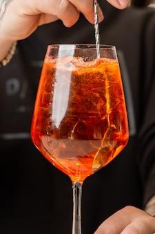 Barkeeper bereitet auf der theke aperol spritz zu, einen klassischen erfrischenden italienischen aperitif, der beim mischen hergestellt wurde