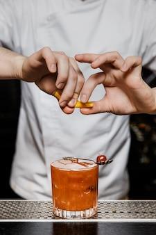 Barkeeper bereitet einen cocktail an der bar zu und drückt eine zitronenschale über ein getränk in einem steinglas
