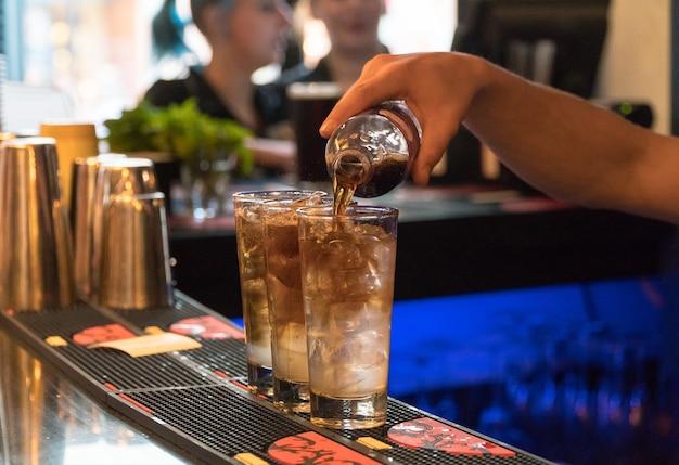 Barkeeper bereitet einen cocktail mit eis vor, nahaufnahme