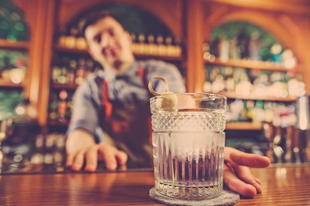 Barkeeper bietet einen alkoholischen cocktail an der bar an der bar