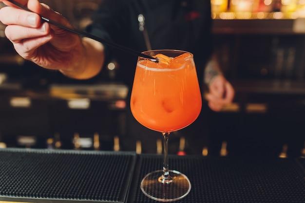 Barkeeper, der alkoholischen aperitif, aperol-spritz-cocktail zubereitet.