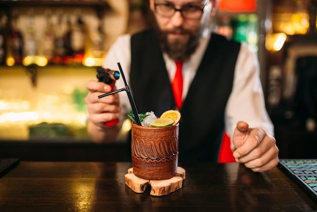 Barkeeper, der alkoholisches getränk mit gasbrenner macht