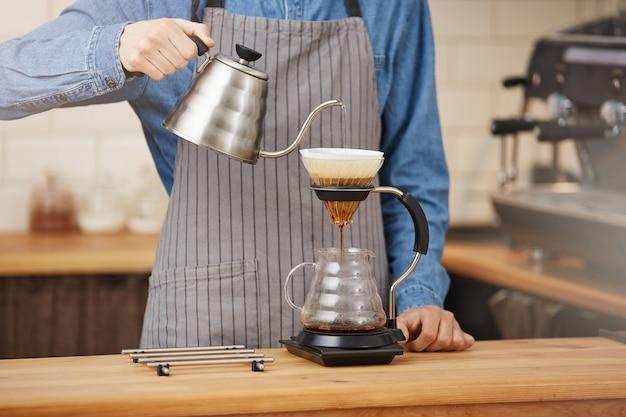 Barkeeper, der alternativen kaffee unter verwendung des manuellen tropfbrühers macht und wasser gießt.