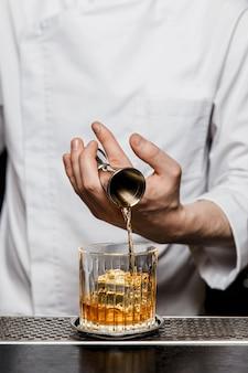 Barkeeper, der an der bar einen cocktail zubereitet und mit einem jigger alkohol in das steinglas gibt
