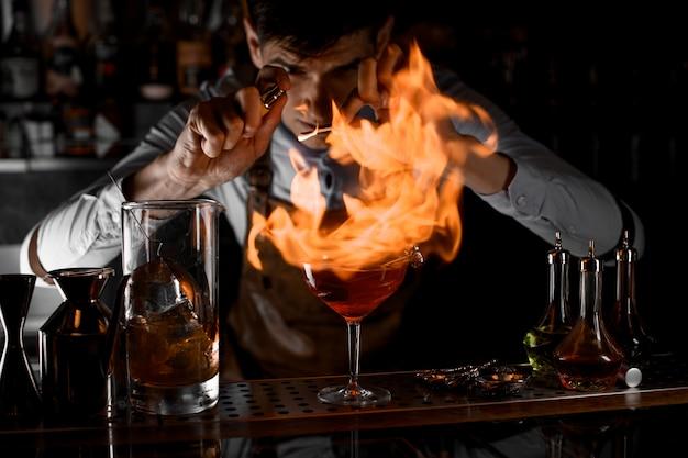 Barkeeper, der auf das feuer um das cocktailglas sprüht