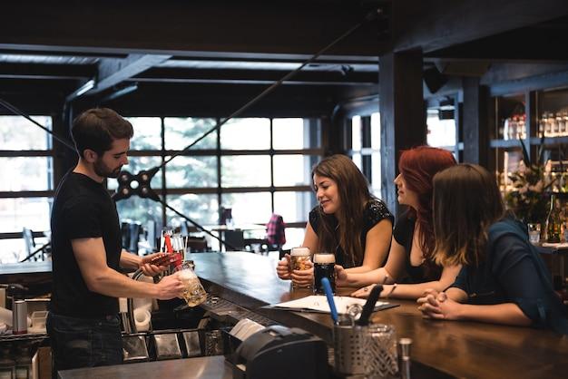 Barkeeper, der bier an der bartheke serviert