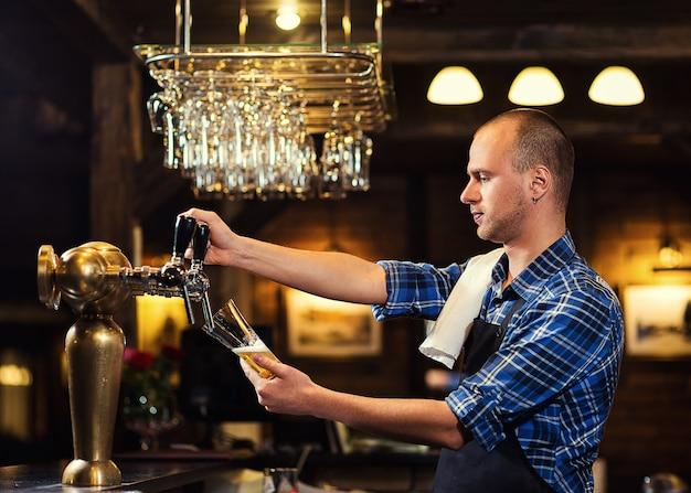 Barkeeper, der das frische bier in der kneipe einschenkt, barmannhand am bierhahn, der ein gezapftes lagerbier einschenkt, bier aus dem zapfhahn, glas mit bier füllen, frisches bier, pub.bar.restaurant.european bar.american bar.