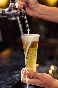 Barkeeper, der das frische bier in der kneipe einschenkt, barmannhand am bierzapfen, der ein gezapftes lagerbier einschenkt, bier aus dem zapfhahn, glas mit bier füllen, pub.bar.restaurant.european bar.american bar.