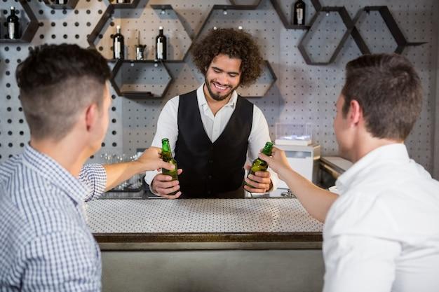 Barkeeper, der den kunden ein glas bier serviert