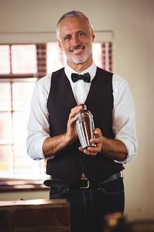 Barkeeper, der ein cocktailgetränk im cocktail-shaker mischt