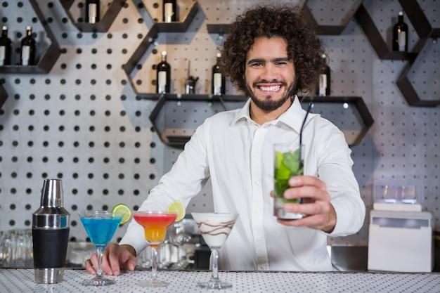 Barkeeper, der ein glas gin serviert