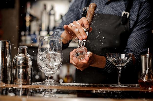 Barkeeper, der ein großes stück eis für einen cocktail auf der bartheke zerquetscht