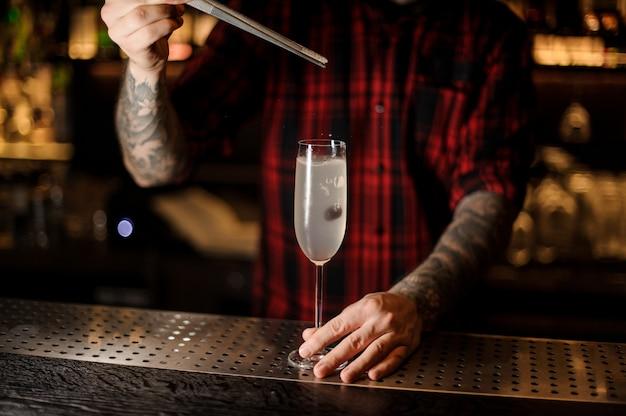 Barkeeper, der eine kirsche in einen französischen 75 cocktail setzt