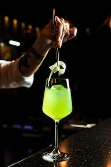 Barkeeper, der einen cocktail zubereitet und sellerie-beilage in ein weinglas mit einem getränk mit grüner eisfarbe gibt