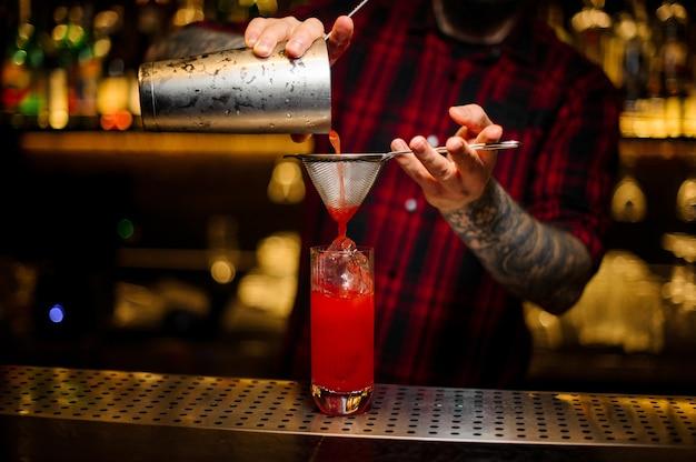 Barkeeper, der einen hurricane punch-cocktail aus dem stahlshaker durch ein sieb auf der bartheke gießt