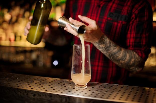 Barkeeper, der einen köstlichen trinidad swizzle-cocktail aus dem stahl-jigger in ein glas auf der bartheke einschenkt